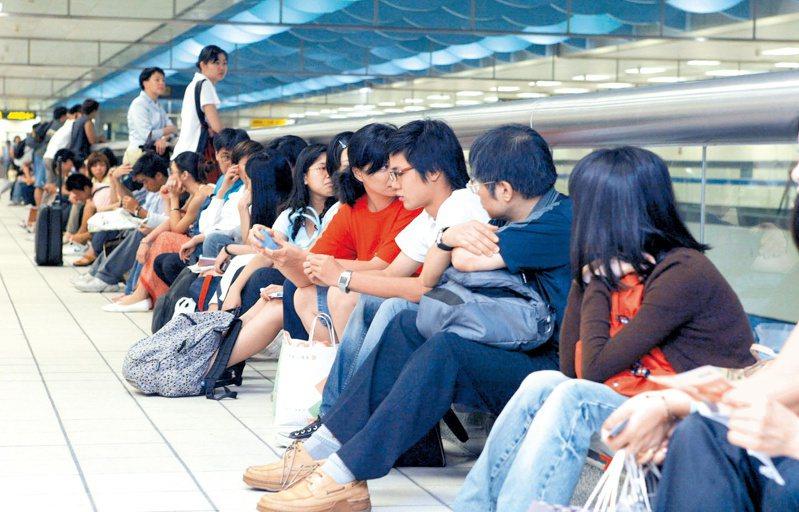 往年萬安演習警報後人車管制,捷運站內旅客被管制在站內不得出站,只好就地坐在護欄邊等待演習結束。記者游順然/攝影