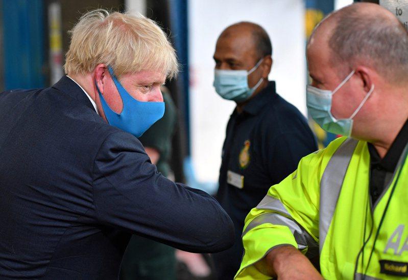 英國首相強生以手肘打招呼取代握手。 路透社