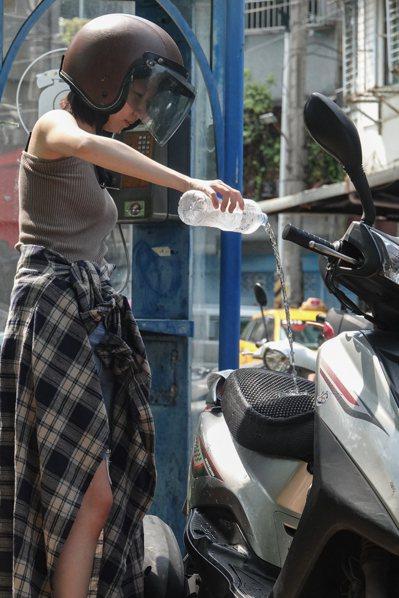 昨天各地天氣炎熱,台北測站昨天中午飆到攝氏卅八點九度高溫,創下台北測站七月最高紀錄,有騎士上車前用冰水幫坐墊降溫。記者葉信菉/攝影