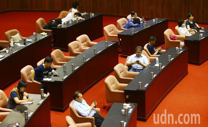 國民黨團一早從議場前門搶進攻占主席台,而綠委則只能坐在委員席上滑手機,等候黨團下一步指示。記者杜建重/攝影