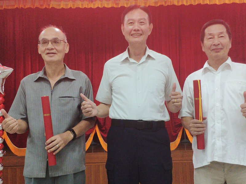 台南市警局副局長林金郎(左一)、許世旻(右一)將退休,市警局準備另類畢業證書,由局長周幼偉(中)親自頒發。記者謝進盛/攝影