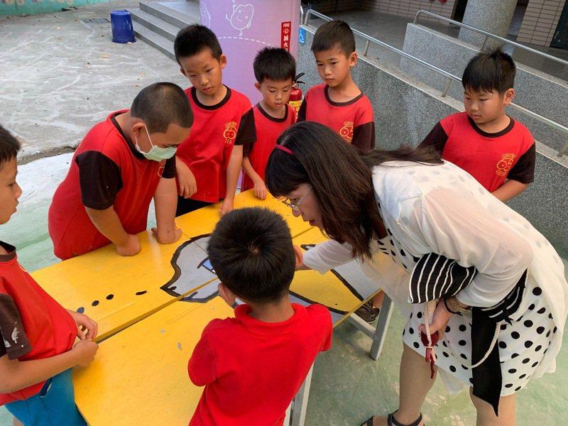 彰化县民靖国小校长李瑞致关心小朋友彩绘废弃课桌椅。图/民靖国小提供
