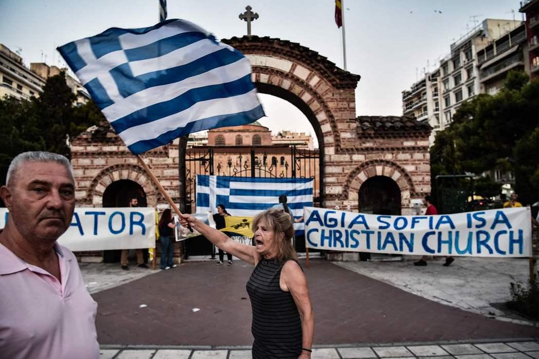 希臘、俄羅斯都對此決議表態不滿。圖為法院決議出爐後,希臘民眾揮旗抗議。 圖/法新...