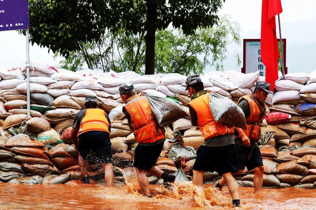 近日鄱陽湖氾濫面積持續擴大,中國軍人在湖附近建防洪堤。 圖/法新社