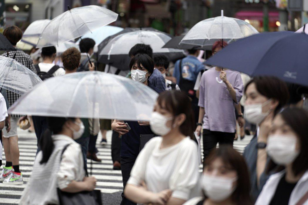 近一周東京的新冠肺炎病例激增。圖為在東京澀谷街上,民眾戴著口罩。美聯社