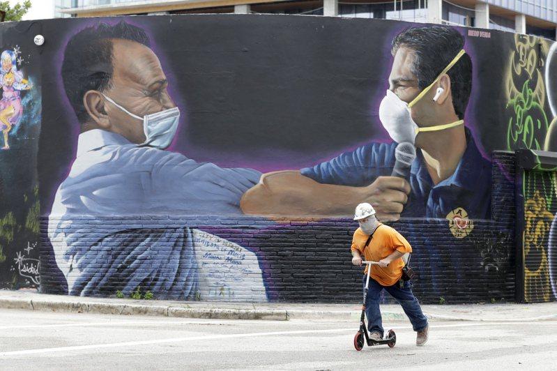 佛州邁阿密市新冠疫情嚴重,圖為邁阿密市區內壁畫,市長蘇阿瑞茲(右)與當地富商瑪納(右)宣導戴上口罩。美聯社