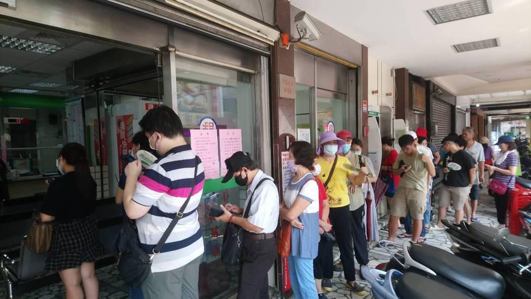 新莊新泰路郵局排隊人潮蔓延至騎樓。記者吳亮賢/攝影