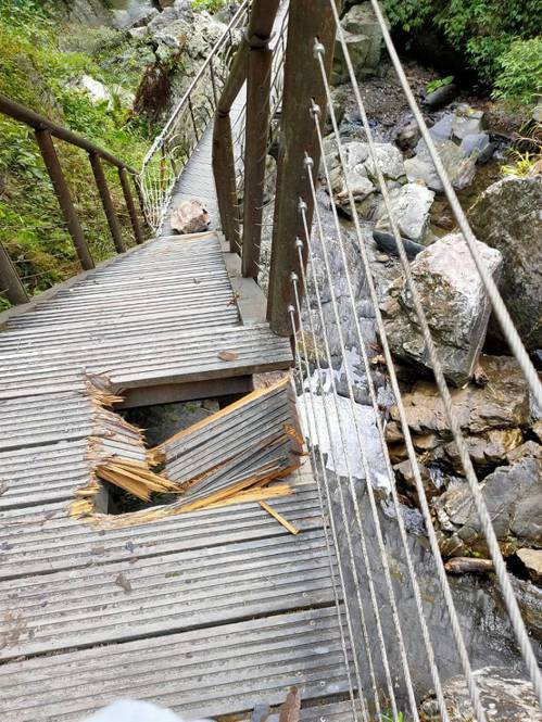 宜蘭縣冬山鄉新寮瀑布步道昨天驚傳落石,步道的木棧板也被落石擊中,留下破洞。圖/宜蘭縣消防局提供