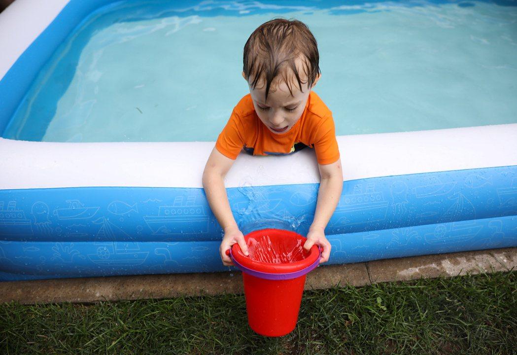 紐約疫情雖緩和,紐約人仍不敢掉以輕心,住在布魯克林的小男孩在自家後院的充氣泳池裡...