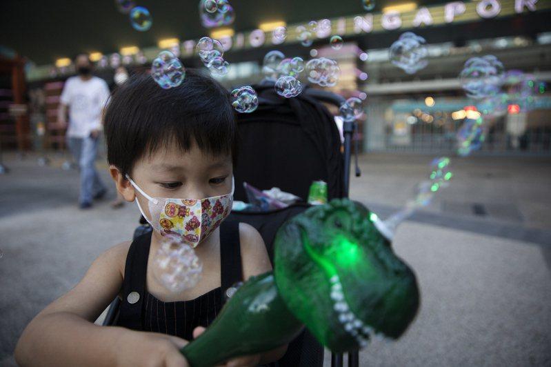 新加坡衛生部今天通報,境內新增327人確診感染新冠肺炎,其中絕大多數仍是住在外勞宿舍的移工,另有9起社區病例及3起境外移入案例。圖為一名小孩在玩恐龍泡泡機。 歐新社