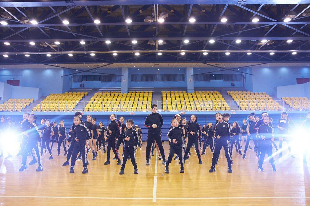 蕭敬騰(中)揪上百名小舞者們齊跳「抖肩舞」,場面壯觀又療癒。圖/華納提供