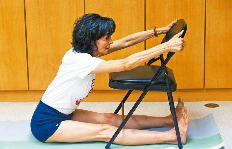 陳淑麗示範椅子瑜伽,有椅子就隨時可做。 圖/林俊良