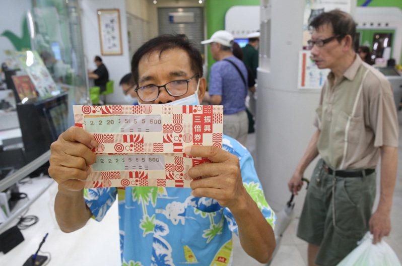 全台一二六九間郵局加班銷售三倍券,民眾拿到後秀出熱騰騰三倍券。圖/聯合報系資料照片