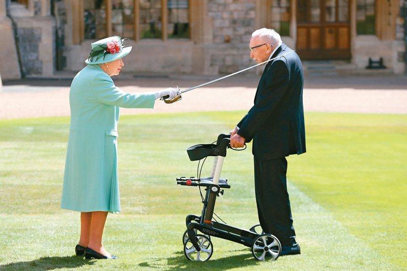 英國女王伊麗莎白二世十七日公開露面,以父親、先王喬治六世的劍,輕輕拍打一百歲的二戰老兵摩爾肩部,冊封他為爵士。(法新社)
