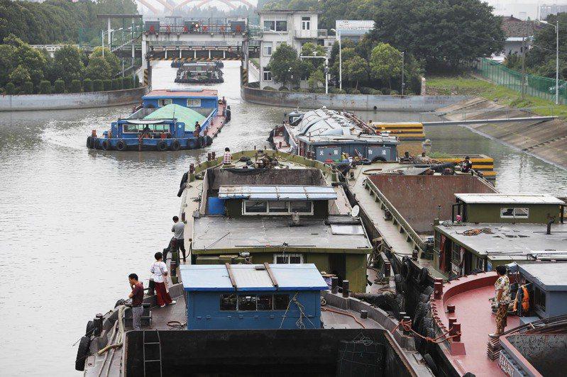 為有效緩解太湖洪水上漲壓力,近日上海部分水閘開閘洩洪。圖為船隻有序通過蕰藻浜西水閘。(中新社)