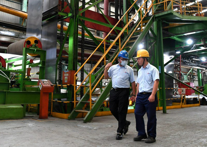 台商陳富澤已扎根大陸22年,認為企業在5G基站建設、新能源汽車、電子物流倉儲等領域將大有可為。圖為陳富澤(左)在車間與工人交流。(中新社)