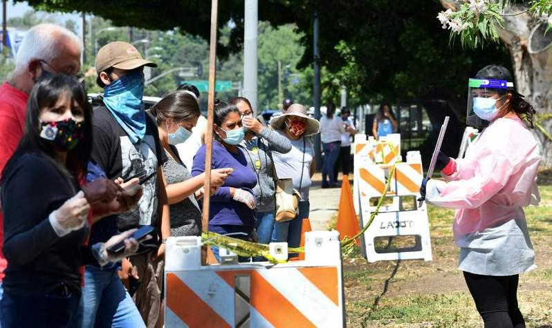 一名志工十七日在美國加州洛杉磯穿著防護裝,指引民眾排隊進入檢測站接受新冠病毒檢測。(法新社)