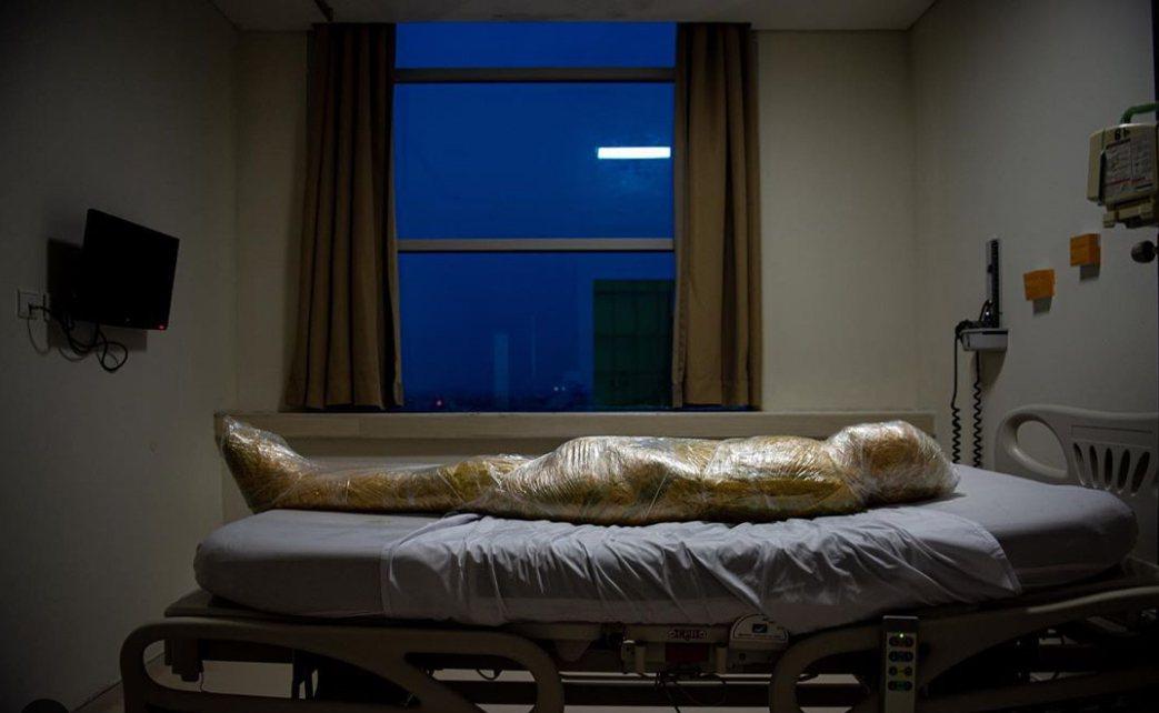 印尼寫實攝影新聞工作者伊爾萬迪在自己的IG貼出一張新冠肺炎罹難者全身包覆塑膠膜躺...