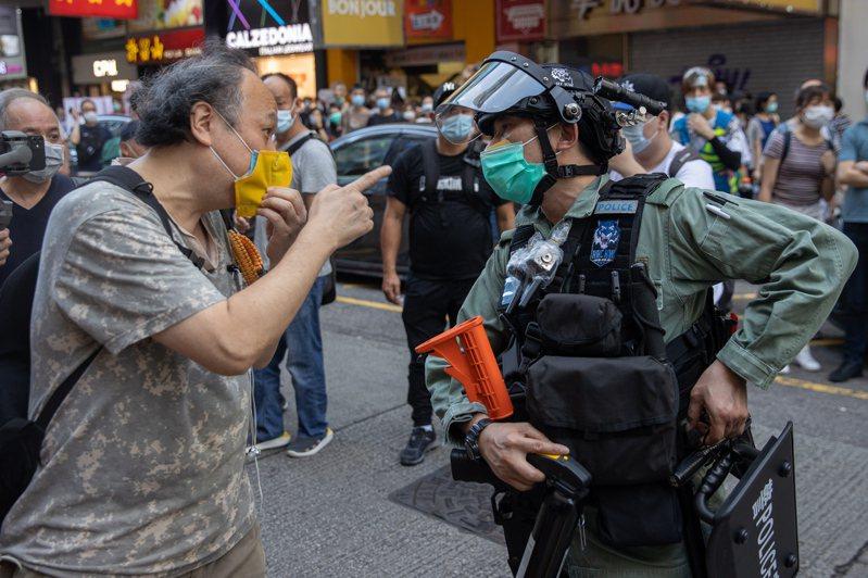 中國大陸當局對香港頒布嚴厲的國安法,使美中緊張情勢再升高。圖為上月廿八日參加港版國安法沉默抗議遊行的男子指著警員。 歐新社