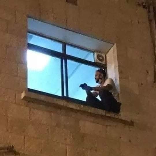 巴勒斯坦男子蘇威提為了向染上2019冠狀病毒疾病(COVID-19)而住院的母親訣別,在恪守隔離規定情況下,爬牆到母親病房窗口邊守著。圖/取自Twitter