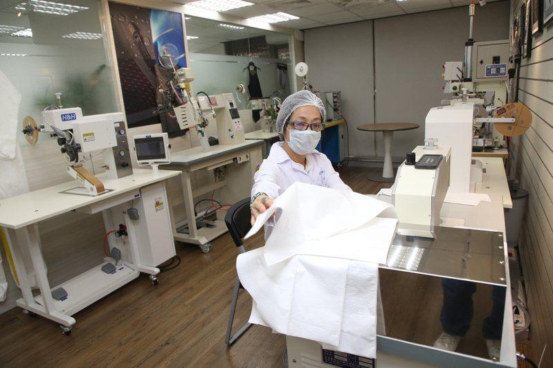 當新冠肺炎疫情肆虐,成衣廠集結起來組成紡織防疫國家隊,協助政府生產防護衣/隔離衣。圖/中央社