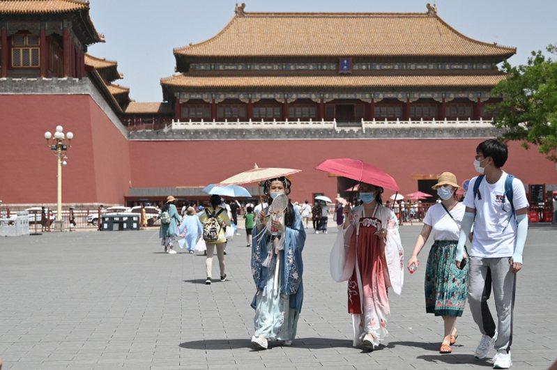 圖為北京故宮午門外,日前有身著古裝的遊客撐傘經過。中新社