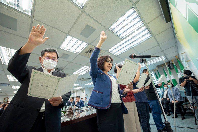 民進黨新任中評會主委康裕成(中間藍衣者)今天宣誓就職。圖/民進黨提供