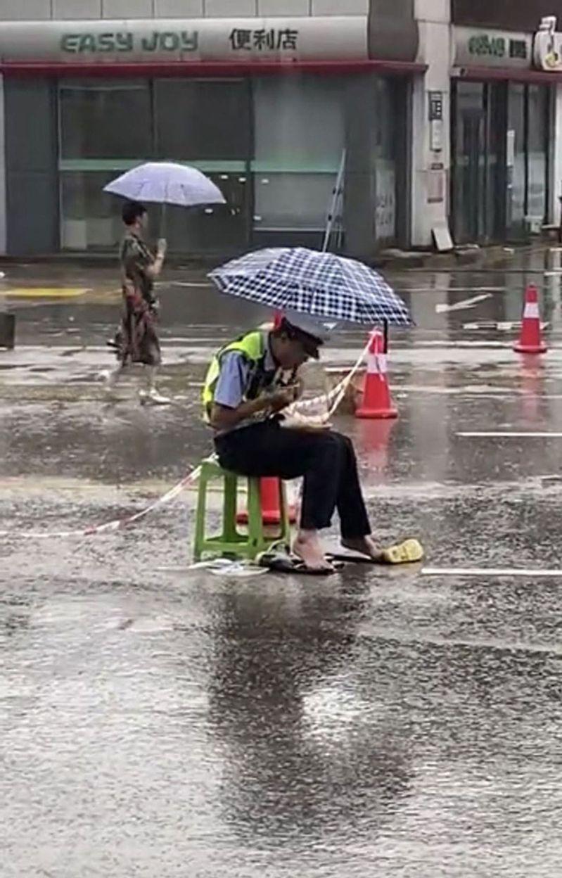 康弘在雨中光腳扒飯。圖/取材自恩施市公安局
