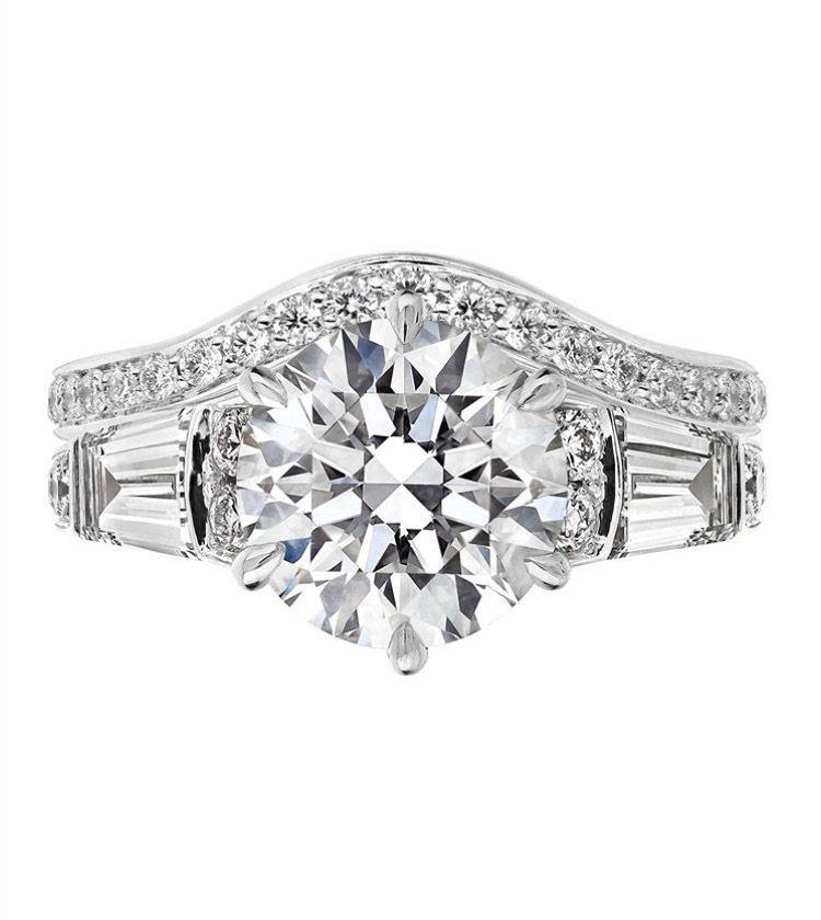 由英國知名設計師Shaun Leane訂製的婚戒,中央為一顆2.5克拉的圓形明亮...