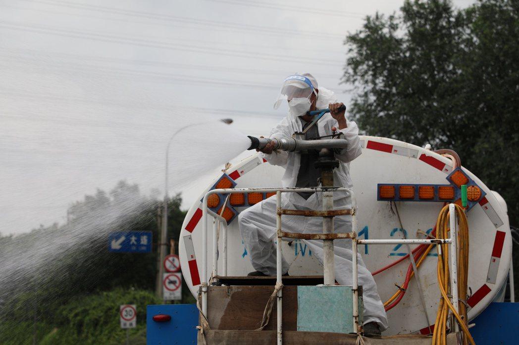 大連再度出現疫情後,圖為23日街頭正在進行全面消毒。路透