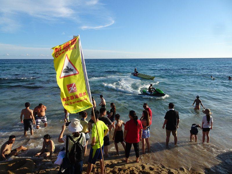 夏日水上活動勝地的屏東墾丁最近重現人潮榮景,各遊憩沙灘劃設水上摩托車的進出航道,白砂沙灘在岸邊插上黃旗,提醒遊客勿靠近。記者潘欣中/攝影