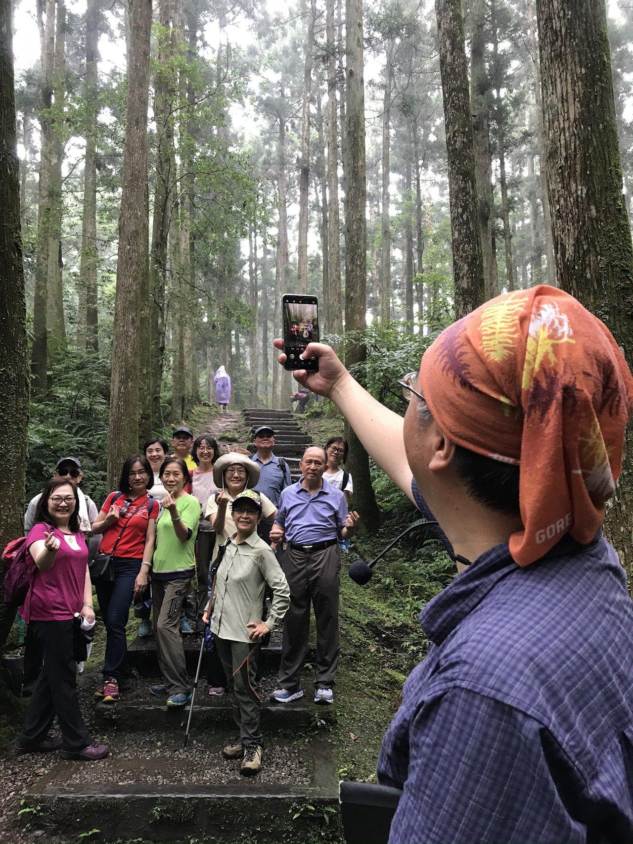 祥哥透過階梯與樹林延伸出線條構圖,幫學員拍團體照。圖/林育如攝影