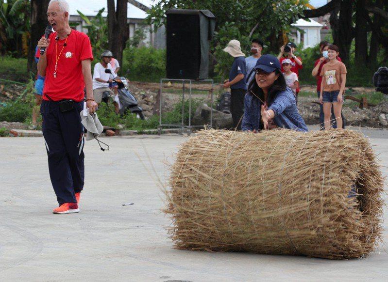 「翻滾吧,草捲」,居民將稻稈製作成稻草捲,讓遊客下場接力。記者徐白櫻/翻攝