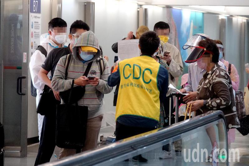 菲律賓新冠肺炎疫情嚴峻,我國中央流行疫情指揮中心規範26日起從菲律賓入境旅客全面採檢。圖為首批旅客26日下午在桃園機場疾病管制署檢疫站接受檢疫官審核申報資料情形。記者陳嘉寧/攝影