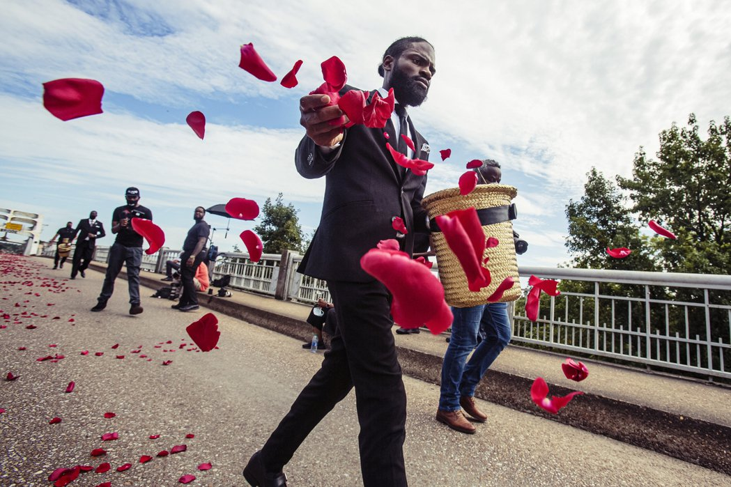 送葬隊伍在大橋上鋪設玫瑰花瓣,用以象徵抗爭留過的鮮血。 圖/歐新社