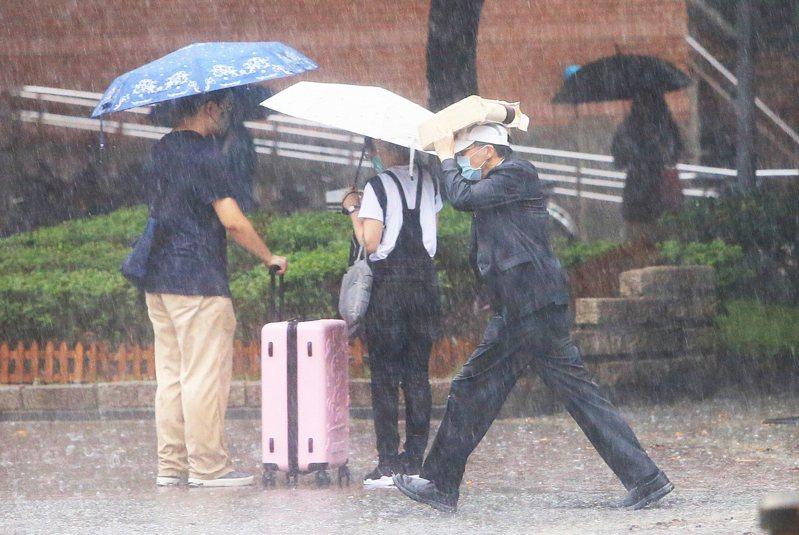 台北下起午後大雷雨,有民眾拿起隨身物品遮頭快跑。圖/聯合報系資料照片