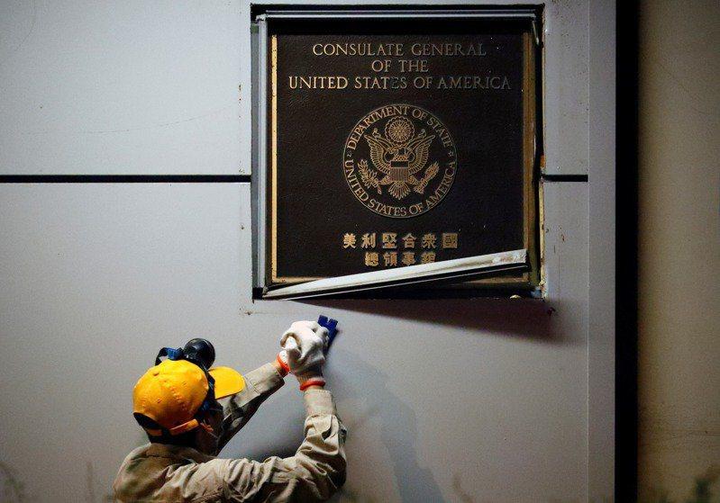 廿六日晚間,工人在卸除美國駐成都總領事館的門匾。(路透)