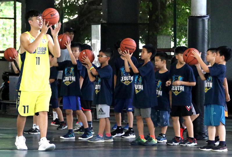 在地高雄出身的柯旻豪,認真指導小學員如何持球。圖/高雄市政府運動發展局