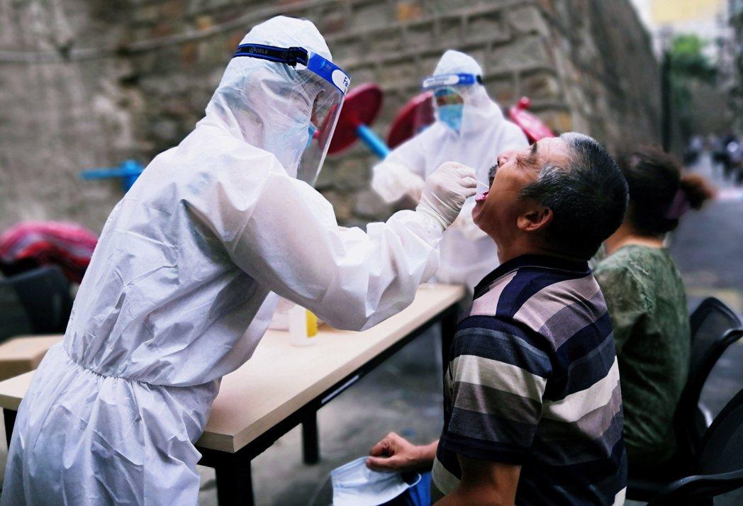 7月19日,烏魯木齊街頭正進行新型冠狀病毒檢測。 圖//路透社