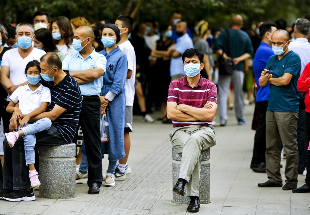 7月初,烏魯木齊市內等待高考學生的家長。 圖/中新社