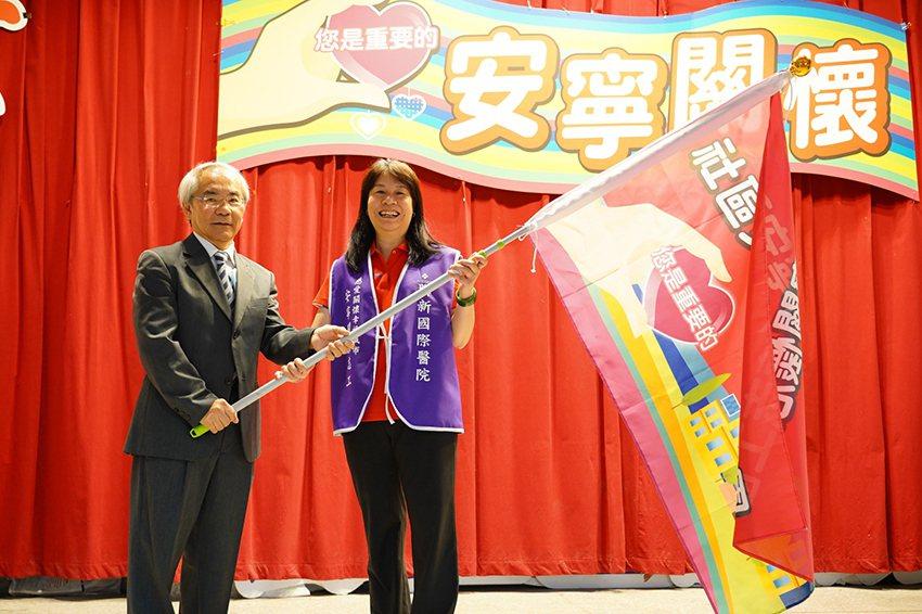 聯新國際醫院院長黃忠智(左)為志工授旗。 聯新國際醫院/提供