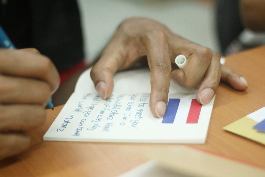 荷蘭遊客寫卡片給孩子留念。 圖/因為所以教育協會提供