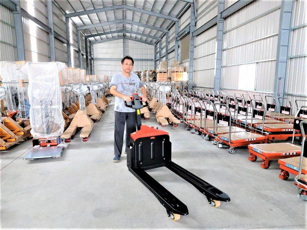 力牛高強董事長高相文展示近期熱銷的「1.5噸自走式電動拖板車-小猛牛」。莊智強/...