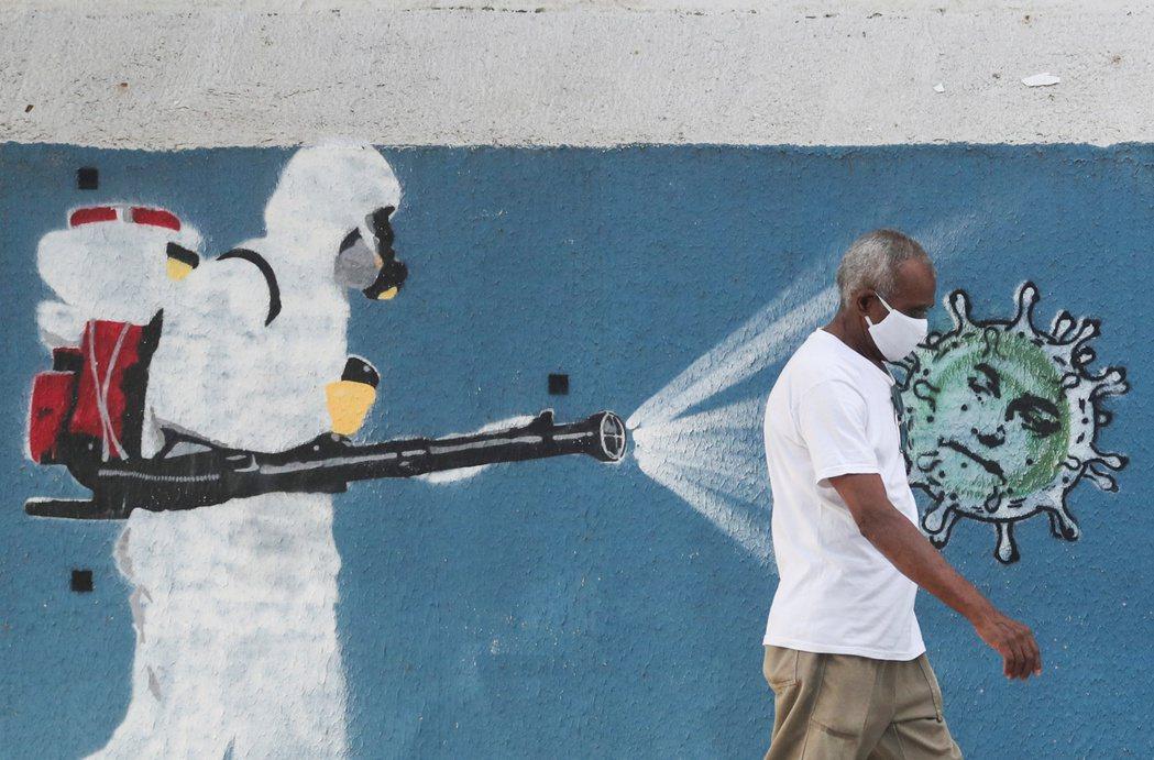 巴西街頭,戴口罩的民眾行經新冠疫情壁畫前,形成對比畫面。路透