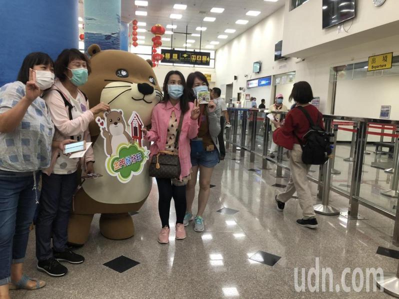 近千名國內外遊客造訪金門,大家在通關大樓輪流跟吉祥物「阿特」合影留念。記者蔡家蓁/攝影
