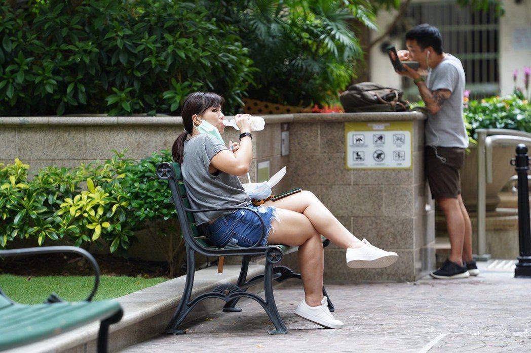 香港禁堂食,很多人只好跑到公園吃午餐。 圖/新華社