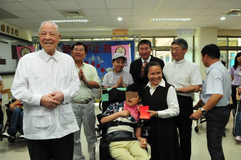 101年5月18日前總統李登輝(左)在敏道家園,與認養15年的多重身心障礙黃姓女孩(中坐輪椅者)相見歡。圖/縣府提供