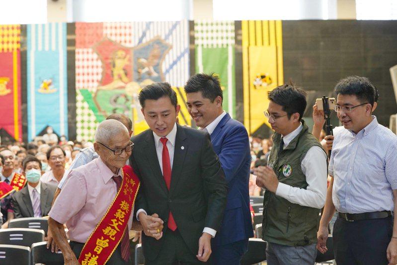 新竹市政府昨天表揚161名模範父親,市長林智堅緊握最年長的百歲人瑞曾謙誠一起上台。圖/市府提供