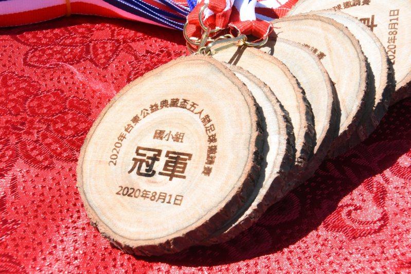 今年第五屆台東公益典藏盃足球邀請賽很環保,獎牌是利用樟樹的斷枝製作。記者羅紹平/攝影