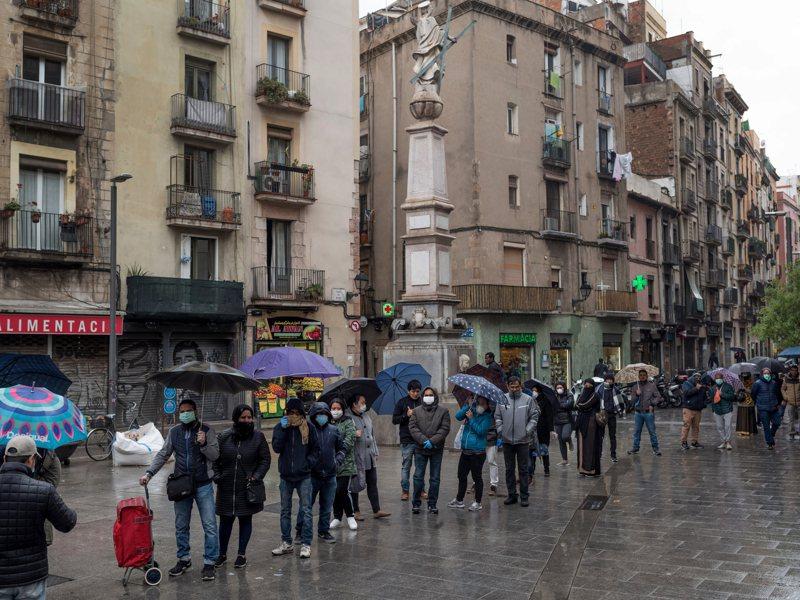 歐洲抗疫經驗凸顯當地許多社福計畫的優點。圖為西班牙民眾3月30日在巴塞隆納一個社福辦公室外,排隊領取食物券。圖/取自紐約時報